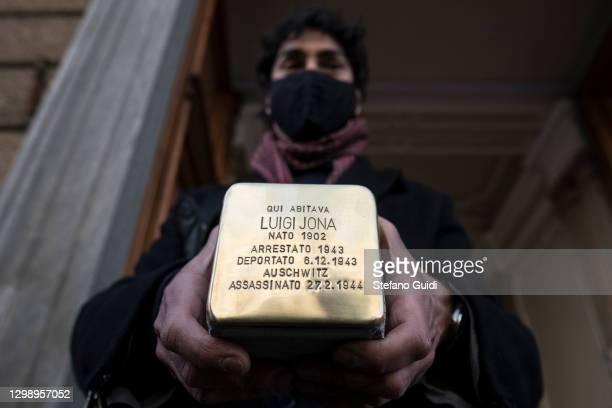 "Man holds a stumbling stone for Luigi Jona, by German artist Gunter Demnig during the installation of the ""Memory Blocks"" in Corso Matteotti 53 on..."