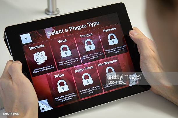 A man holds a tablet device showing a screen from the video game Plague Inc as he poses in the company's London offices on November 7 2014 The Ebola...