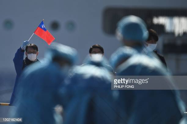 Man holds a Taiwan flag as passengers disembark from the Diamond Princess cruise ship, in quarantine due to fears of new COVID-19 coronavirus, at the...