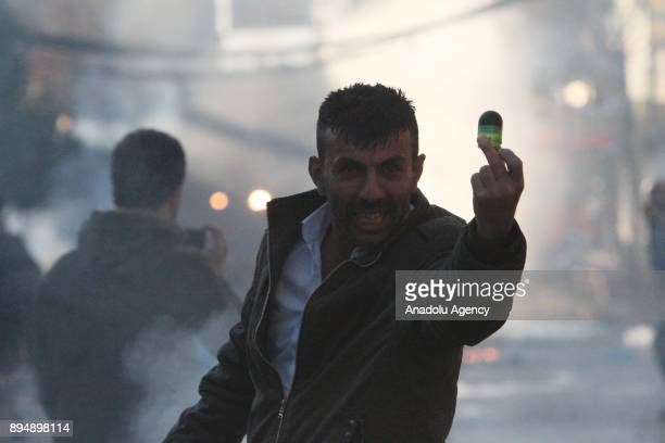 A man holds a tear gas can piece while demonstrators clash with riot police within antigovernment protests in Sulaymaniyah Iraq on December 18 2017...