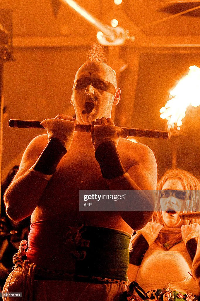A man holds a torch as he performs durin : News Photo