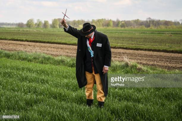 A man holds a twig cross just before he puts it on a field crop during the traditional horse riding procession on Easter Monday in Zernica village...