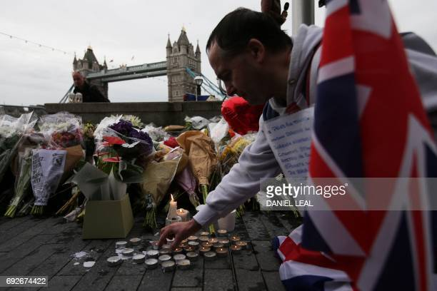 A man holds a Union flag as he kneels near flowers and candles layed at Potters Fields Park in London on June 5 during a vigil to commemorate the...