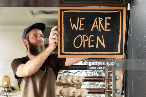 a man holds a we are open sign as he opens his food truck for service - small business stock pictures, royalty-free photos & images