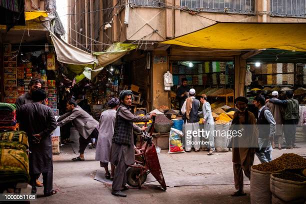 A man holds a wheelbarrow as people shop at Mandai Bazaar in Kabul Afghanistan on Thursday July 12 2018 US President Donald last year said 16000 US...