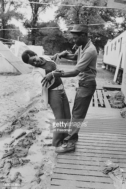 A man holds a woman precariously over mud in Resurrection City a three thousand person tent city on the Washington Mall set up as part of the Poor...