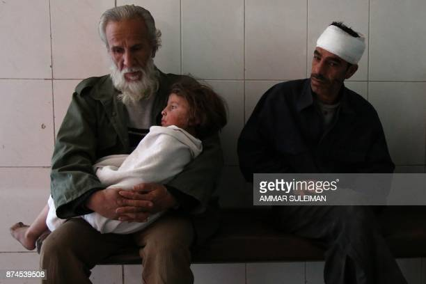 TOPSHOT A man holds a wounded child in his arms in the emergency ward of a hospital in the Eastern Ghouta town of Kafr Batna on the outskirts of...