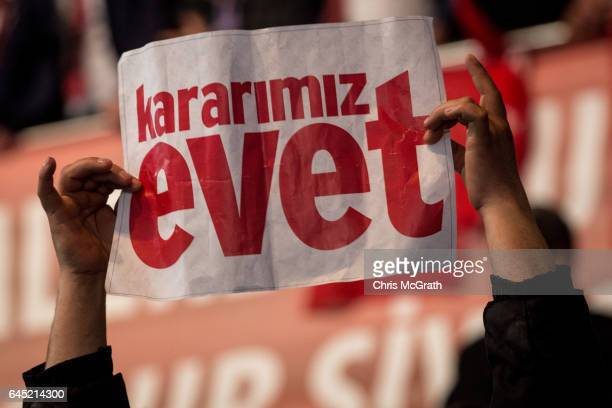 A man holds a 'Yes' banner during a rally officially opening the AKP Party 'Yes' constitutional referendum campaign held at the Ankara Arena on...