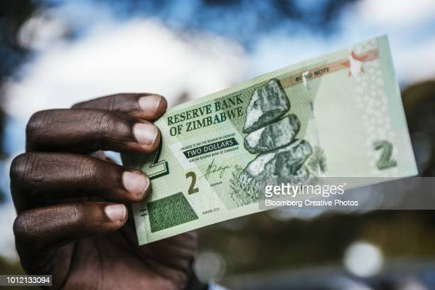 a man holds a zimbabwean two dollar bond banknote - zimbabwe stock pictures, royalty-free photos & images