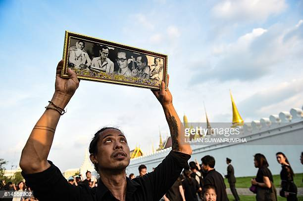 A man holds aloft images of Thai King Bhumibol Adulyadej after the hearst carrying the late monarch arrived at the Grand Palace in Bangkok on October...