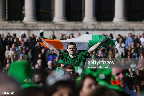 A man holds aloft the Irish Flag over the crowds gathered to celebrate St Patrick's Day in Trafalgar Square on March 18 2007 in London England...