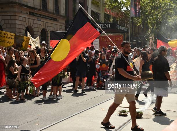 A man holds an Aboriginal flag during an 'Invasion Day' rally on Australia Day in Melbourne on January 26 2018 Thousands of supporters joined rallies...
