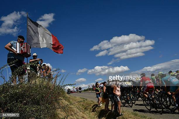 A man holds an accordion next to a French national flag as the pack rides during the 1625 km seventh stage of the 1625 km eleventh stage of the 103rd...