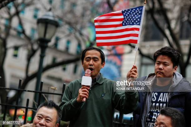 A man holds an american flag as he attends a protest in support of immigration in herald Square on February 10 2018 in New York / AFP PHOTO / KENA...