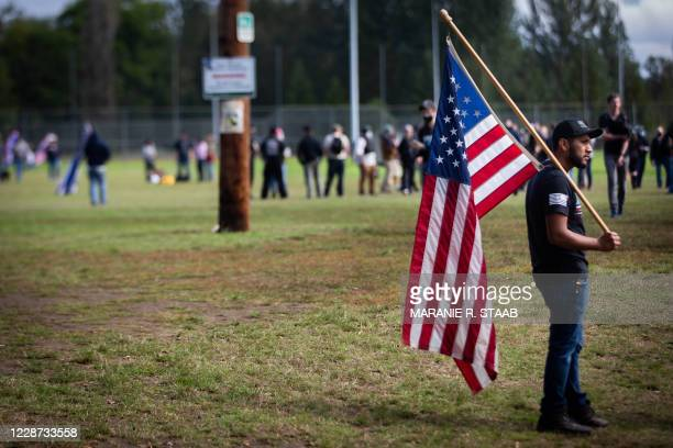 Man holds an American flag at a rally held by the Proud Boys and other similar groups at Delta Park in Portland, Oregon on September 26, 2020. -...