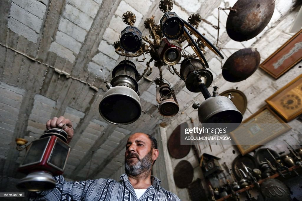 A man holds an antique lantern in a shop in the rebel-held town of Saqba, in Eastern Ghouta on the outskirts of the capital Damascus, on May 24, 2017, as Syrians prepare for the holy month of Ramadan due to start later this week. /