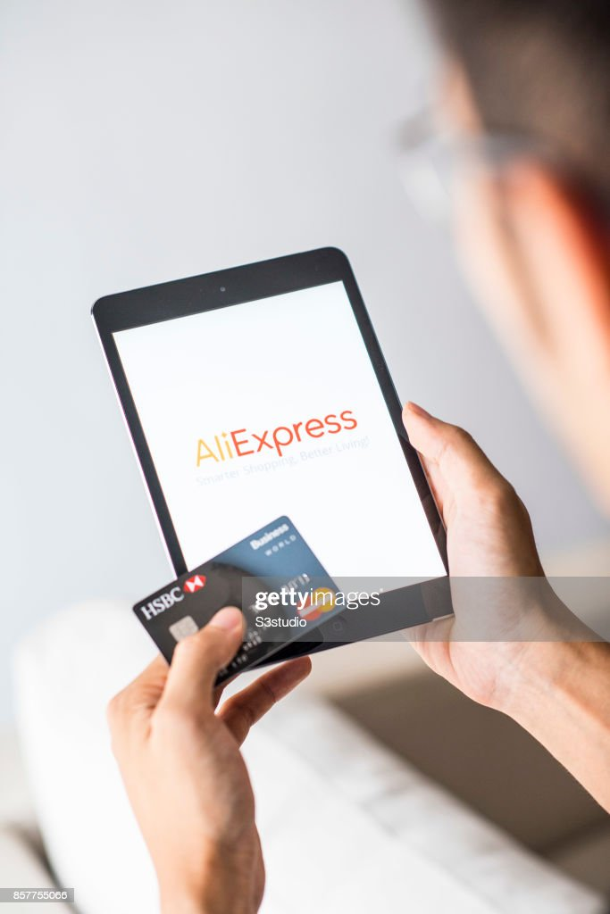 A man holds an Apple iPad Mini as he uses AliExpress app