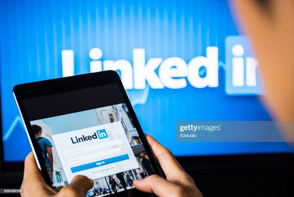 Young man holds a smart device while using Linkedin app : Fotografía de noticias