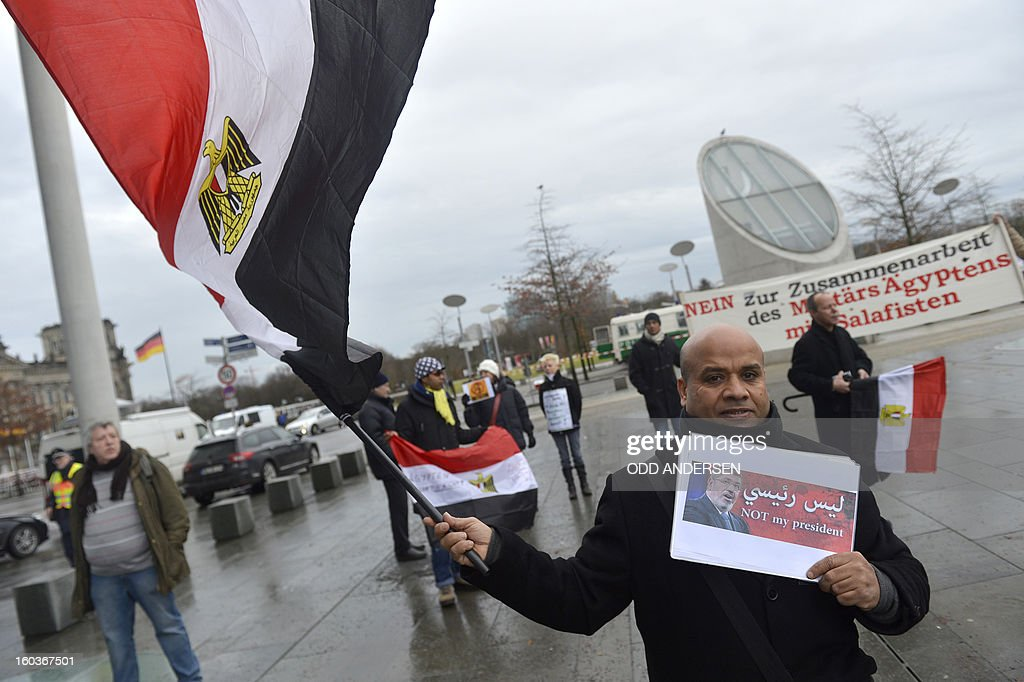 A man holds an Egyptian flag and a poster showing the face of Egyptian President Mohamed Morsi and reading 'Not my president' during a protest demonstration near the Chancellery where German Chancellor is to meet with Egyptian President on January 30, 2013. Egyptian President Mohamed Morsi's is to meet with Angela Merkal as his scheduled visit to Germany was still on despite deadly clashes in the country, but the two-day trip had been cut back to just a few hours. ANDERSEN