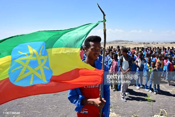 A man holds an Ethiopian flag as children from neighbouring Hama elementary school arrive to pay condolences at the crash site of the Ethiopian...