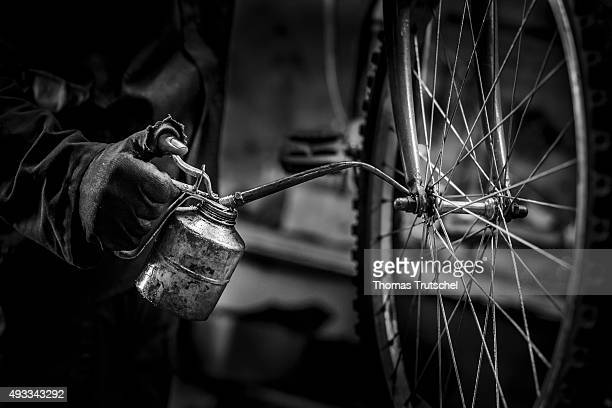 A man holds an oil can in his hand while he repairs a bicycle in a bicycle shop on September 29 2015 in Beira Mozambique
