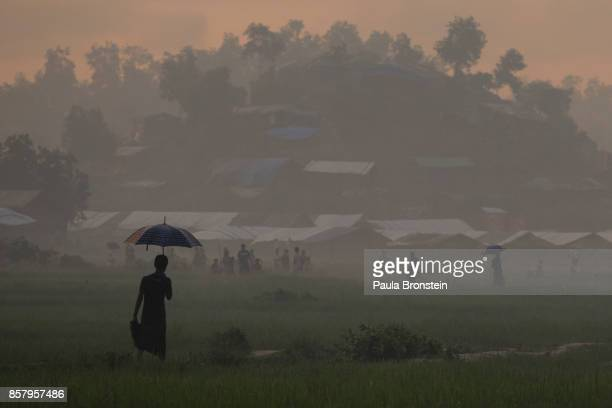 A man holds an umbrella during light rain near the Balukhali refugee camp on October 5 2017 at Palongkhali Cox's Bazar Bangladesh Over a half a...