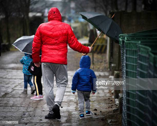 A man holds an umbrella to protect a child from the rain in Bydgoszcz Poland on March 9 2019