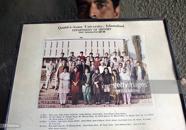 A man holds an undated picture showing Pakistani cleric Abdul Rashid Ghazi standing with fellow students of the history department at the QuaideAzam...