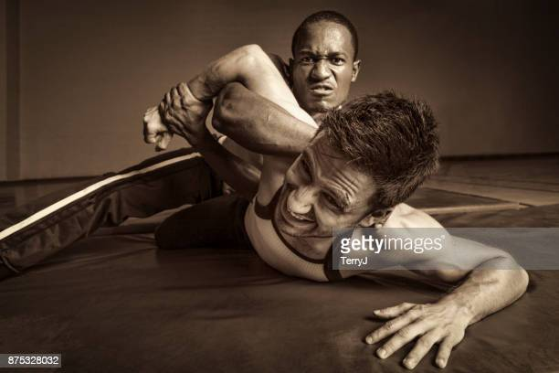 Man holds another man down in a wrestling match