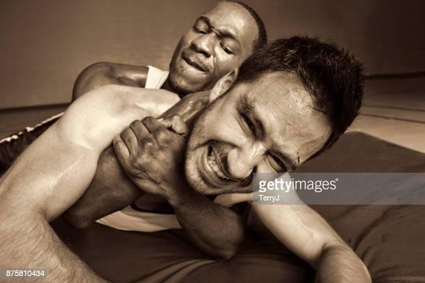man houdt een andere man ingedrukt in een worsteling - mixed wrestling stockfoto's en -beelden