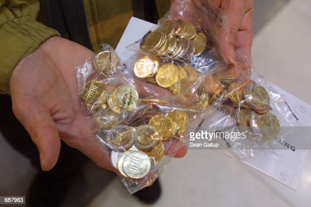 A man holds bags of Euro coins he just bought December 17 2001 in Frankfurt Germany the day banks started distributing the first socalled Starter...