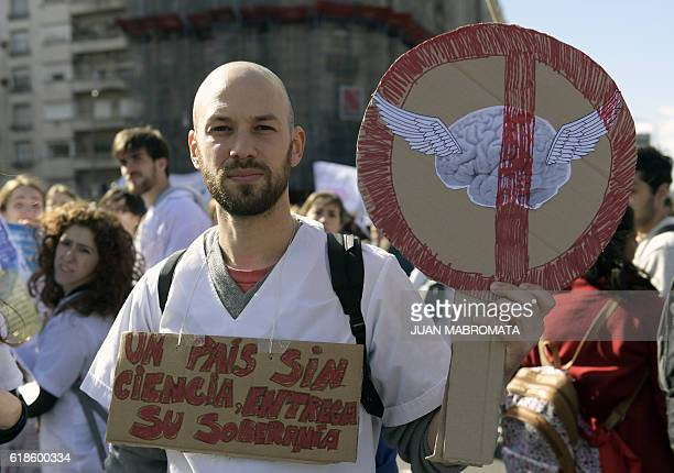 A man holds banners in front of the Argentine National Congress during a protest of university students teachers scientists and academics against...