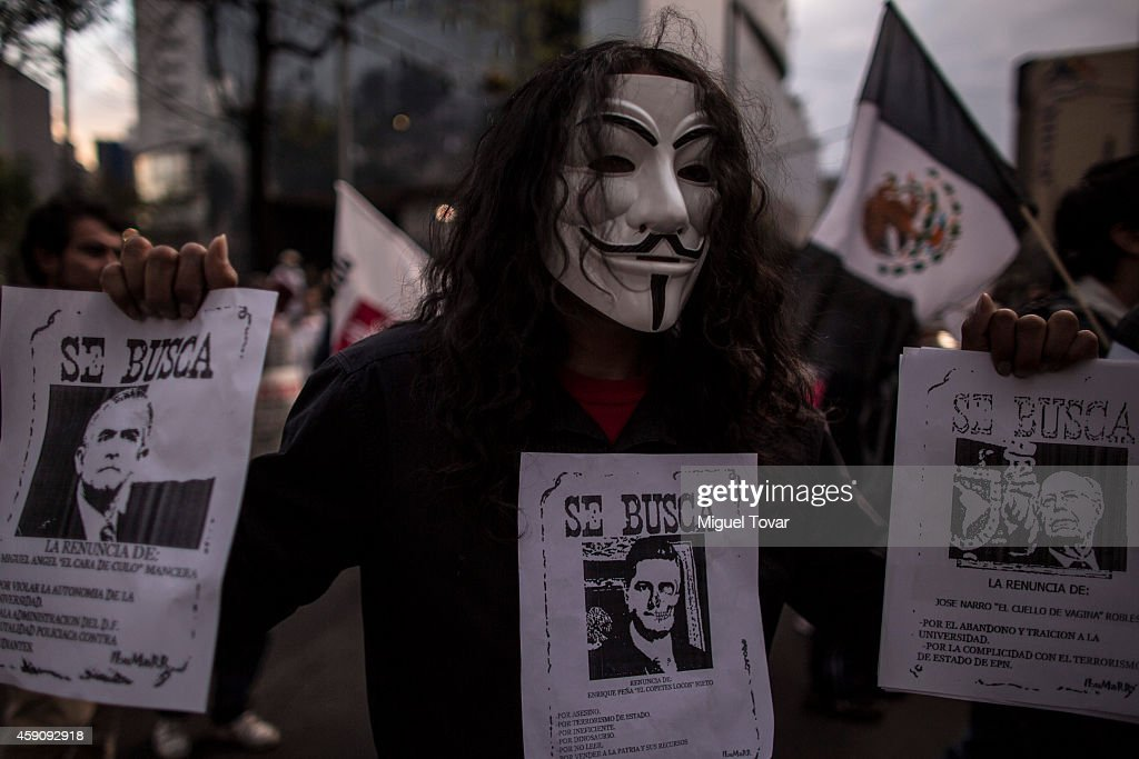 A man holds banners of Mexican president Enrique Peñ–a Nieto and Mexico City mayor Miguel Angel Mancera during a demonstration against Mexico's government who suggest that 43 missing students were murdered and their charred remains tipped in a rubbish dump and a river in Guerrero, Mexico, on November 16, 2014 in Mexico City, Mexico.