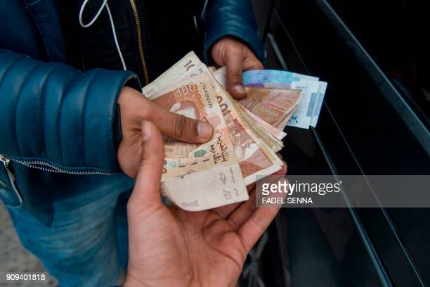 A man holds bills of Moroccan dirham on January 23 2018 in Casablanca After years fighting to evict tenants he believes are backed by corrupt...