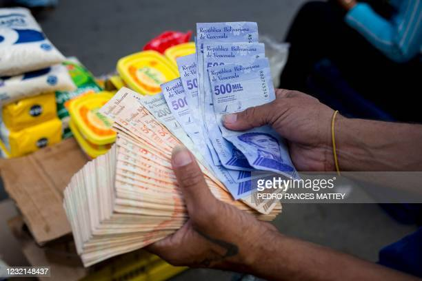 Man holds Bolivar bills a street market in Caracas' Catia neighborhood, on April 6 amid the Covid-19 pandemic.