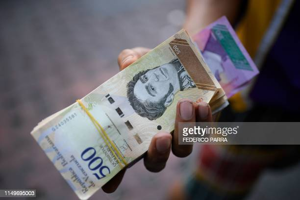 Man holds Bolivar bills in a street of Caracas on June 13, 2019. - Venezuela is again issuing new banknotes recognising the inflation spiral. The new...