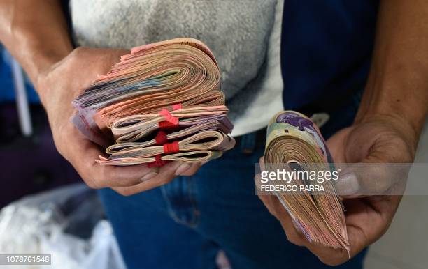 Man holds Bolivar-notes to pay a ticket at a bus station in Caracas on January 3, 2019. - Washington has recently stepped up contacts with South...
