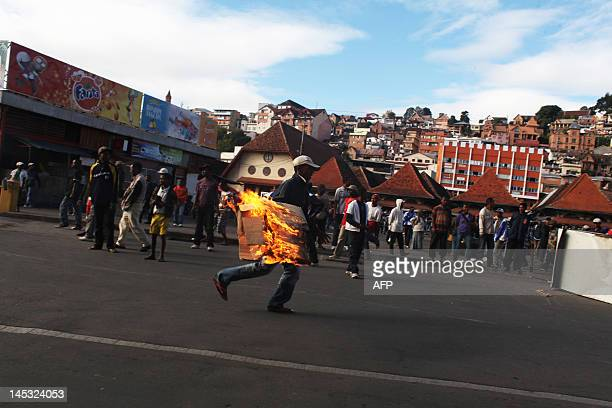 A man holds burning cardboard as he takes part in an ultranationalist protest in Antananrivo on May 26 2012 About 1000 people from the...