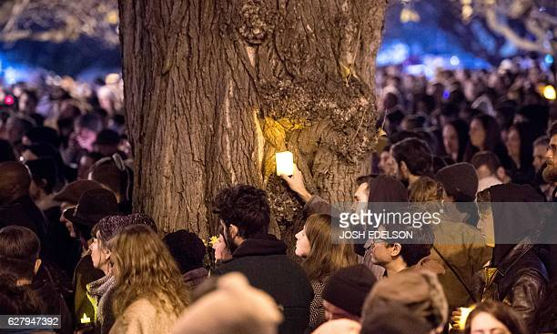 A man holds candle amidst a crowd of thousands during a vigil honoring those who died in in a warehouse fire in Oakland California on December 05...
