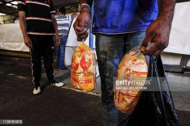 TOPSHOT A man holds chickens after buying a food package of a total of 150 sold by the government's Local Committee for Supply and Production...