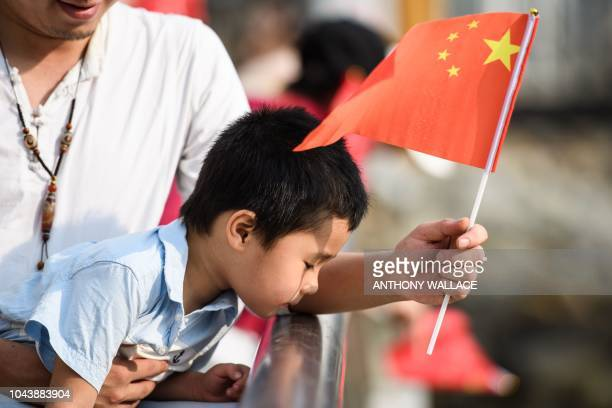 A man holds China's flag and a child after a flag raising ceremony as part of China's National Day celebrations in Hong Kong on October 1 2018 China...