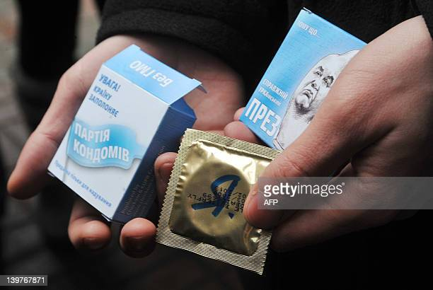 A man holds condom boxes decorated with a caricatured image of Ukrainian President Viktor Yanukovych during an unauthorized rally in Kiev on February...