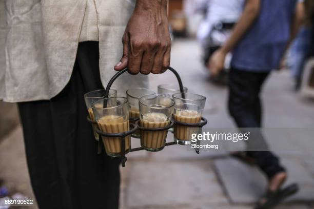 A man holds cups of tea in Varanasi Uttar Pradesh India on Saturday Oct 29 2017 A big drop in borrowing costs for Indian state lenders on perpetual...