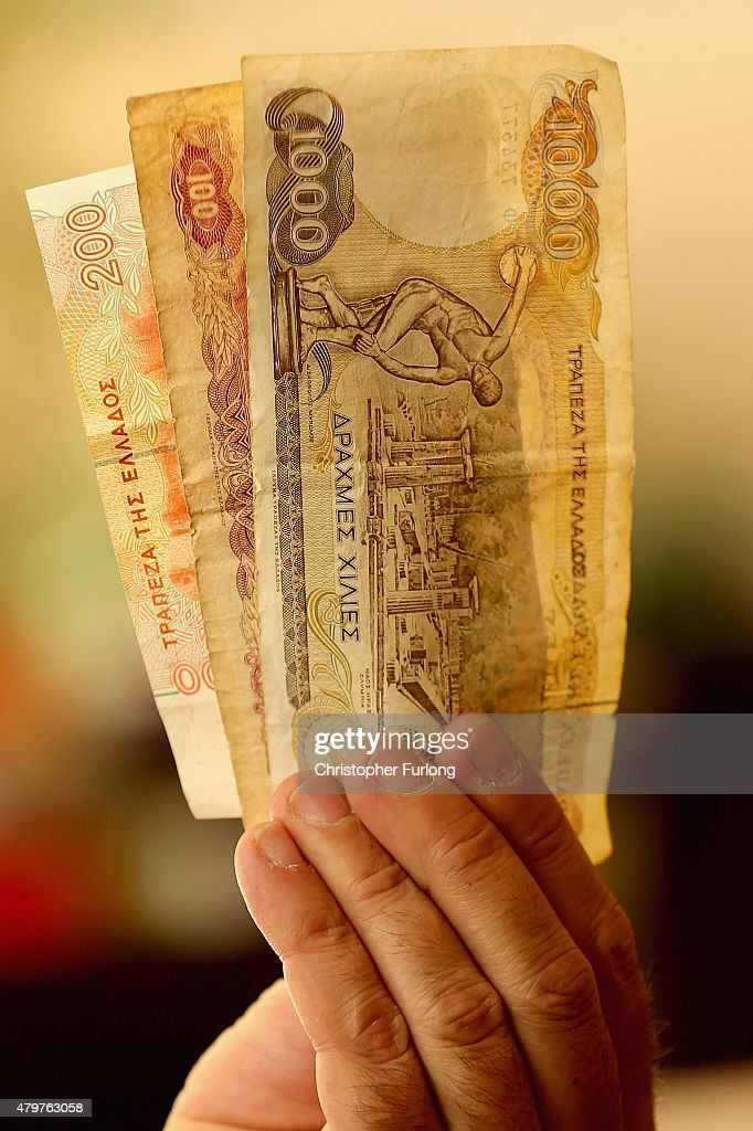 A man holds Drachma notes, the currency in Greece before the Euro, on July 7, 2015 in Athens, Greece. Greek Prime Minister Alexis Tsipras is working on new debt crisis proposals and is due to present them at a Eurozone emergency summit today.