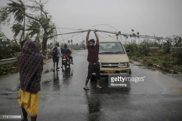 A man holds electrical cabling so that a car can pass underneath on highway after Cyclone Fani passes in the Puri district of Odisha India on Friday...