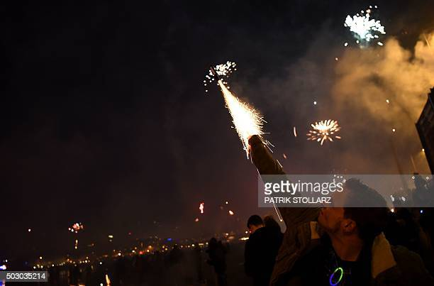 A man holds fireworks as it explodes near the Cologne Cathedral during New Year's celebrations in Cologne on January 1 2016 AFP PHOTO / PATRIK...