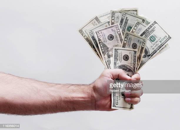 Man holds fist of dollars