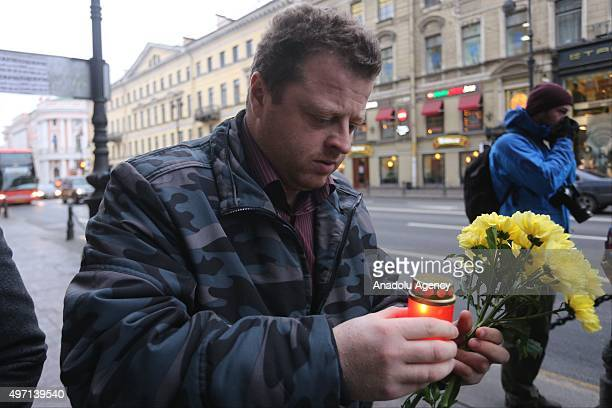 A man holds flowers and lights candle at the entrance of Consulate General of France at Nevsky prospect in St Petersburg Russia on November 14 2015