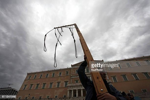"""Man holds gallows in front of the Greek Parliament during demonstration for Global Change, Athens, Greece, Oct 15, 2011 Thousands of """"Indignant..."""