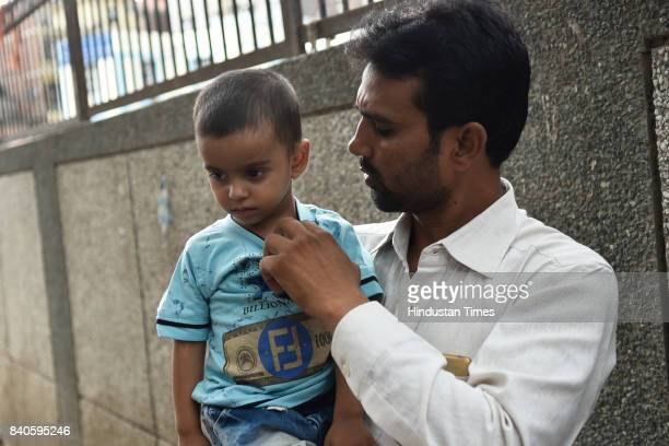Man holds his 2-year-old daughter Zara, who is suffering from Dengue in Zakir Nagar, on August 29, 2017 in New Delhi, India. As per the report...